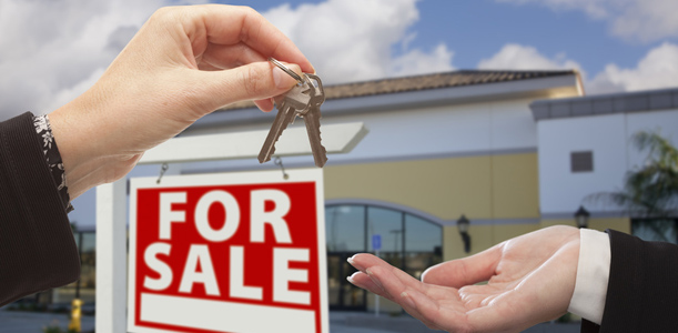 Transitioning a business to a new owner by handing over the keys with a For Sale sign in the background.