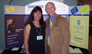 Merlin and Nancy Switzer in front of a Switzer Associates booth