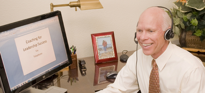 Dr. Merlin Switzer using headphones in front of the computer providing coaching over the phone with the banner, Coaching for Leadership Success, written on the screen.